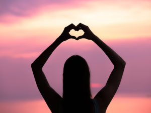 silhouette of girl making heart with hands